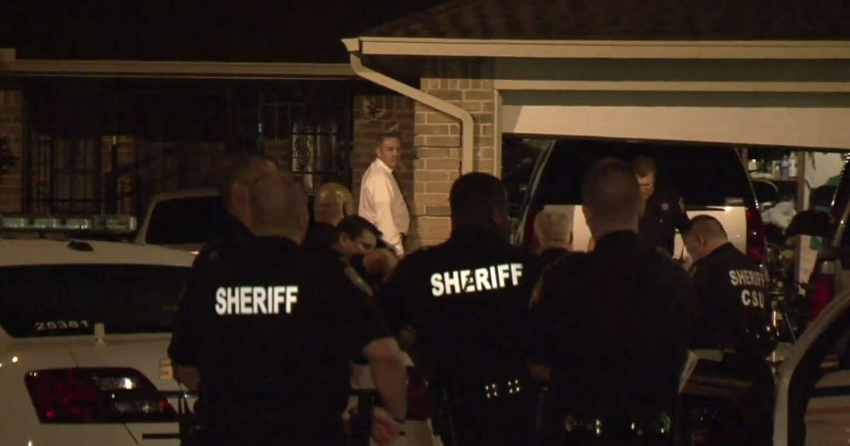Harris County Sheriff Office deputies stand outside the home of two brothers who died in an apparent murder suicide Thursday night.