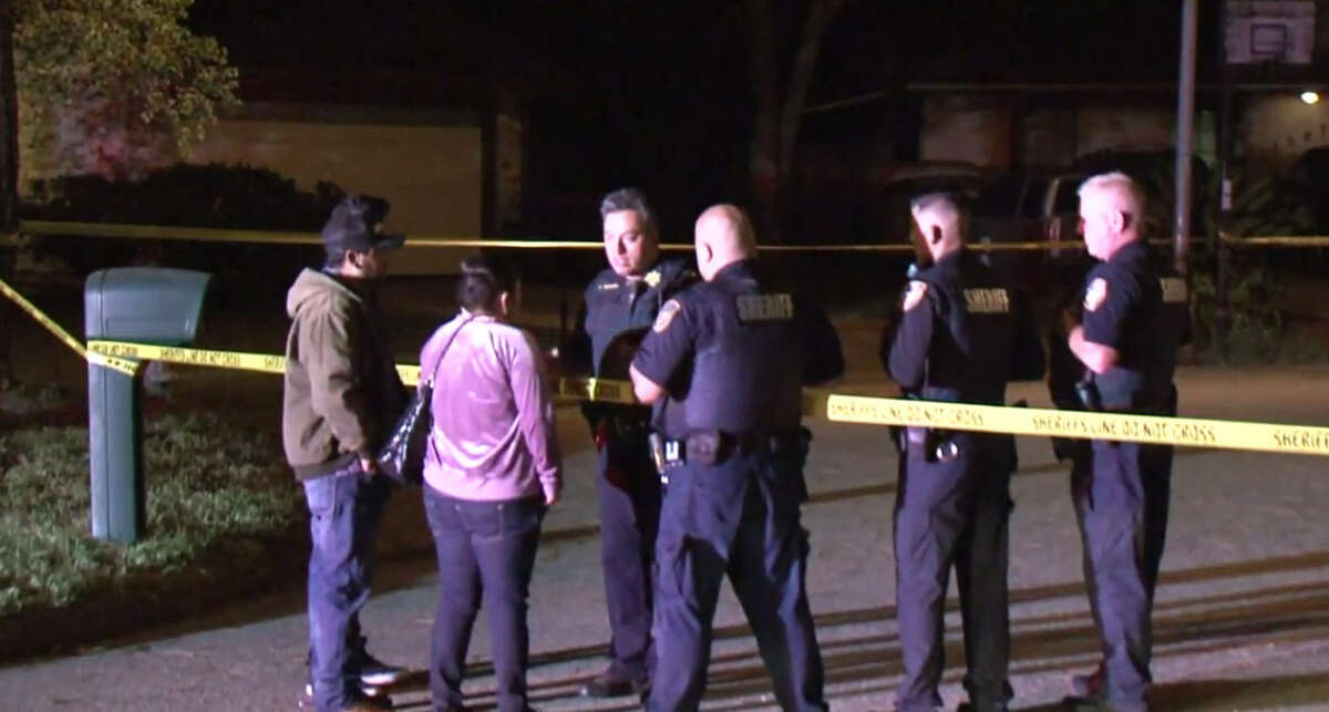 Harris County sheriff deputies talk to residents outside the home where two brothers died.