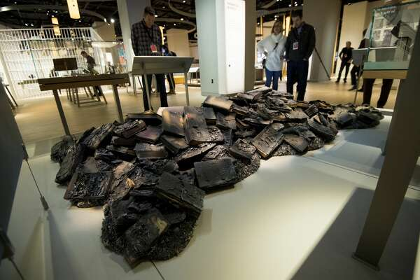 Visitors take in an exhibit of burned bibles the Museum of the Bible on Wednesday, Nov. 15, 2017.