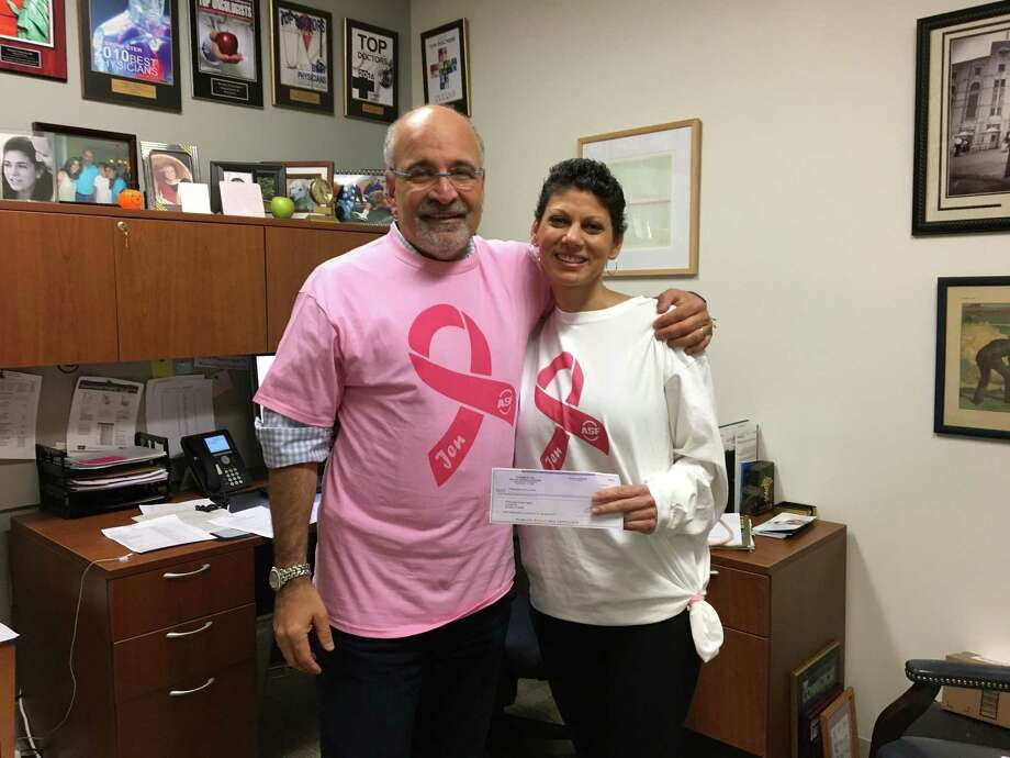 Dr. Richard Zelkowitz, left, medical director of the Smilow Family Breast Health Center, accepts a donation from the ASF Sports & Outdoors store presented by Jennifer Bonitata. Photo: Contributed Photo