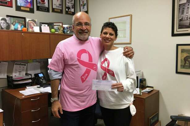 Dr. Richard Zelkowitz, left, medical director of the Smilow Family Breast Health Center, accepts a donation from the ASF Sports & Outdoors store presented by Jennifer Bonitata.