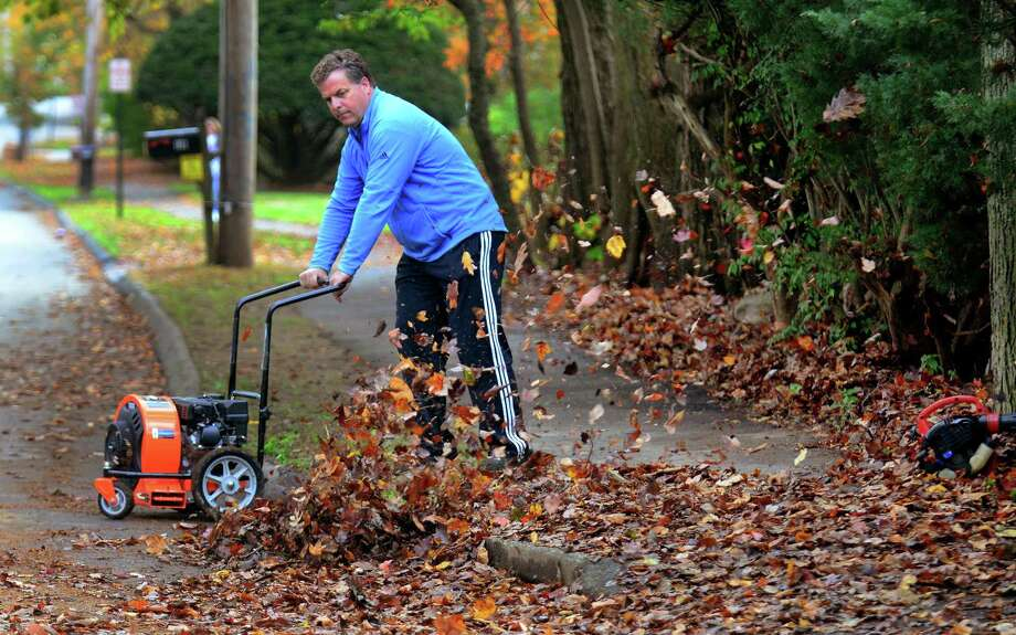 "Kevin Conklin blows leaves off of his sidewalk along Melville Ave in Fairfield, Conn., on Friday Nov. 9, 2017. Conklin, who was working on moving the leaves over to his yard said he, ""Can't wait to get my kids home to help. Why should I have all the fun?"" Photo: Christian Abraham / Hearst Connecticut Media / Connecticut Post"