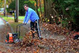 """Kevin Conklin blows leaves off of his sidewalk along Melville Ave in Fairfield, Conn., on Friday Nov. 9, 2017. Conklin, who was working on moving the leaves over to his yard said he, """"Can't wait to get my kids home to help. Why should I have all the fun?"""""""