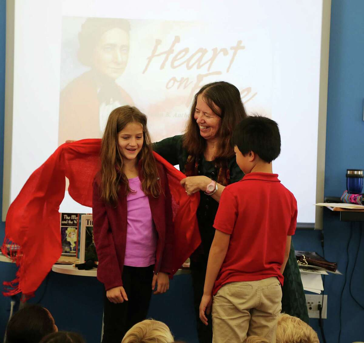 Ann Malaspina, author of books such as Heart on Fire, shared writing tips and offered New Canaan Country School students Isabella Kelley, of Westport, and Jayden Liu, of Stamford, a chance to try on a red shawl similar to the one worn in 1872 by women?'s rights activist Susan B. Anthony.
