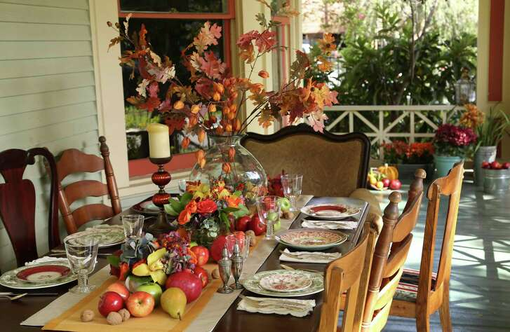 A tall, skinny vase holds a bouquet of fall colors above the crowd. Lucas-Eilers Design Associates combined bittersweet, cockscomb, snowberry, sunflowers, viburnum, and asters. Tableware courtesy of Kuhl-Linscomb.