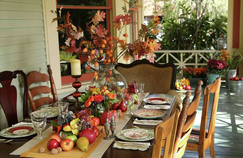 A tall, skinny vase holds a bouquet of fall colors above the crowd. Lucas-Eilers Design Associates combined bittersweet, cockscomb, snowberry, sunflowers, viburnum, and asters. Tableware courtesy of Kuhl-Linscomb. Photo: Karen Warren, Staff / © 2013 Houston Chronicle