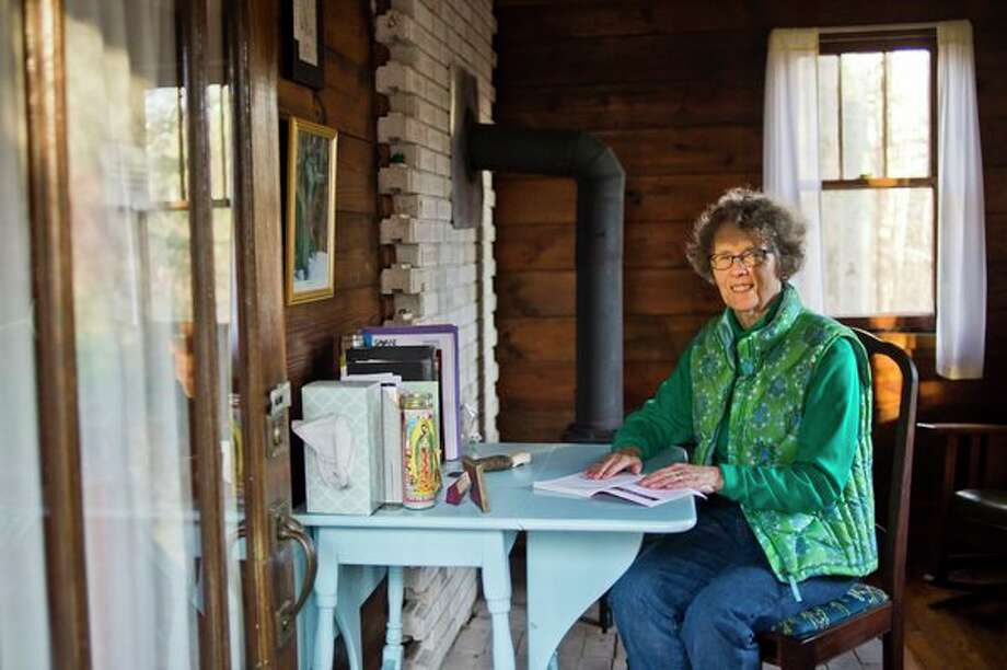 Midland resident Jeanne Schaller poses for a portrait inside the small prayer house in her backyard. Catherine House is very rustic, with no running water or electricity, but has welcomed many visitors over the years and is the focus of Schaller's new book, 'Desert in My Backyard: One Woman's Journey into Silence.' (Katy Kildee/kkildee@mdn.net)