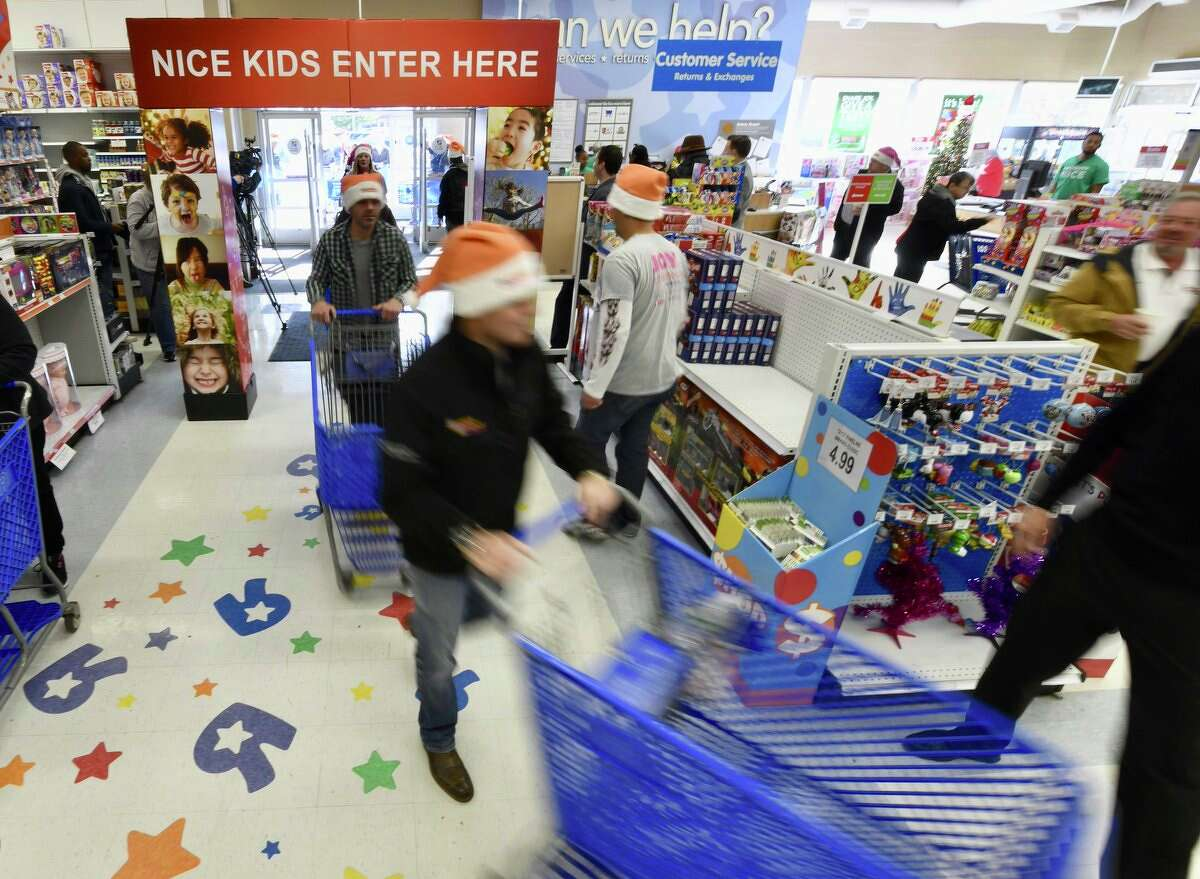"""Volunteers ran through Toys """"R"""" Us on Friday, Nov. 17, 2017, in a shopping spree for the U.S. Marine Corps Reserve Dunkin' Donuts Toys for Tots Train annual trip. (Skip Dickstein/Times Union)"""