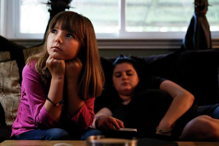 Ava Pettit, 8, left, watches TV with her sister, Mia Perez, 17, right, Tuesday, June 27, 2017 in Webster. About a year ago the family dog, Zoe, bit Ava in the face while jumping for a treat. Ava's parents rushed her to a hospital in their insurance network, but while there, four out of the five doctors who treated Ava were not in network, leaving the family with a $5000 bill. The family ended up paying $3600 after negotiations. ( Michael Ciaglo / Houston Chronicle )