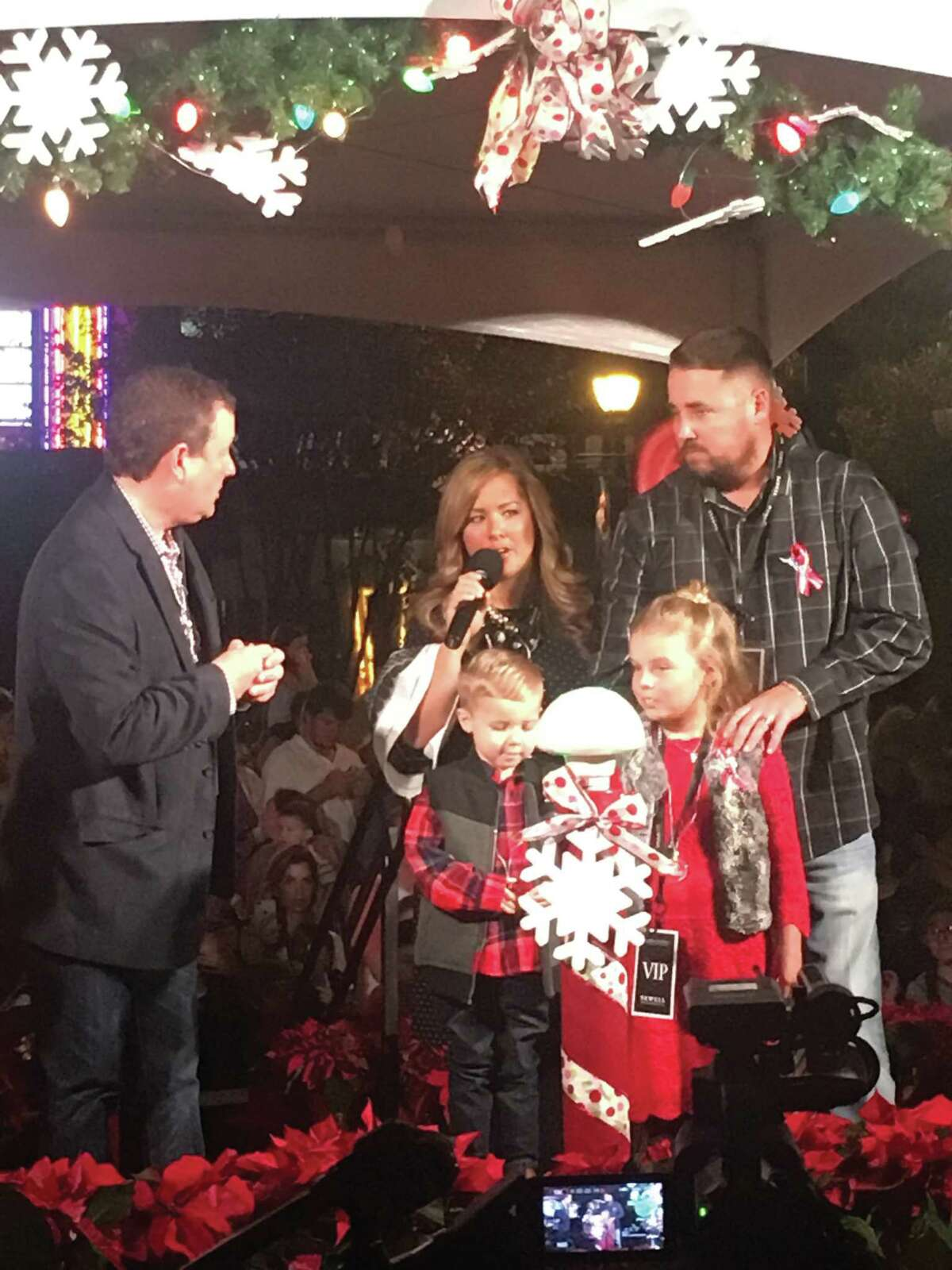 Nick Wolda (left) introduced Kristen, Zach, Addison and Chance Belcher as the honorary 2017 Official Lighting Luminary at the Nov. 16, 2017, Luxury in Lights tree lighting ceremony on Market Street.