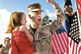 Navy Cmdr. Michael Flatley of East Hampton is shown in this file photo holding his daughter Riley in July 2011 after returning home from an 11-month deployment in Iraq. There will be a yellow ribbon ceremony this weekend to welcome him back: this time from Afghanistan.