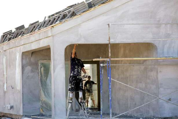 A contractor works on a home under construction at the D.R. Horton Express Homes Magma Ranch housing development in Florence, Arizona. The Commerce Department said Friday that construction of new homes climbed 13.7 percent in October.