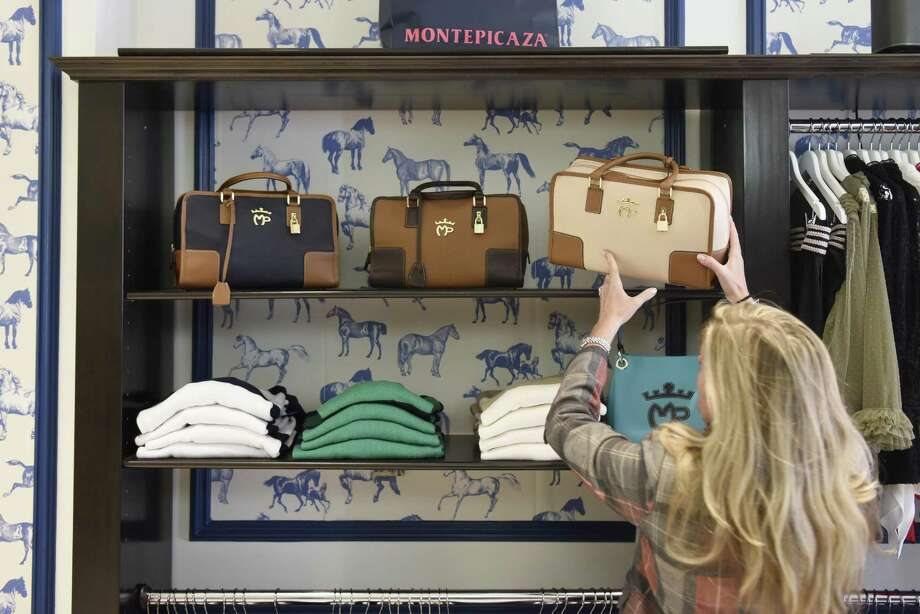 Owner Ellen Christian-Reid moves a handbag at Montepicaza, an upscale Spanish sportwear brand, in Greenwich, Conn. Wednesday, Nov. 15, 2017. Photo: Tyler Sizemore / Hearst Connecticut Media / Greenwich Time