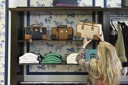 Owner Ellen Christian-Reid moves a handbag at Montepicaza, an upscale Spanish sportwear brand, in Greenwich, Conn. Wednesday, Nov. 15, 2017.