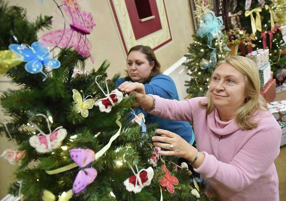 "Members of the Ladies Philoptochos Society, Marina Benas and her daughter Nicole Kelleher, at left, decorate the ""Butterfly Garden"" Christmas Tree, Thursday, Nov. 16, 2017, for the Holiday Fantasy of Trees at Saint Barbara Greek Orthodox Church featuring a raffle of 27 Christmas decorated trees, a holiday marketplace, Greek food and pastries, Saturday, Nov. 18 from 12-8 and Sunday, Nov. 19 from 12-6. Proceeds of the event will benefit local and national charities. The society ask for those who attend to bring a non-perishable food item which will be donated to the Connecticut Food Bank. Photo: Catherine Avalone / Hearst Connecticut Media / New Haven Register"