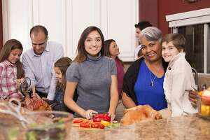 Multi-ethnic, multi-generation family members prepare dinner together in grandmother's home kitchen.  Children, mid-adults and senior woman of Latin, African descent, mixed races and Caucasian ethnicities.  Turkey, ham and salad items on kitchen counter.  Family members talk, laugh, and cook together.