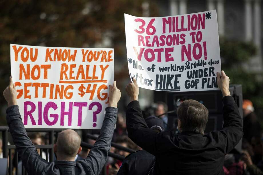 "Demonstrators hold signs during a rally against the GOP tax plan in Washington, D.C., U.S., on Wednesday, Nov. 15, 2017. Senate Republicans tacking on a repeal of the Obamacare mandate that people have health insurance to tax overhaul plan is the ""mother of all monkey wrenches,"" Senate Democratic leader Chuck Schumer said. Photographer: Zach Gibson/Bloomberg ORG XMIT: 775075986 Photo: Zach Gibson / © 2017 Bloomberg Finance LP"