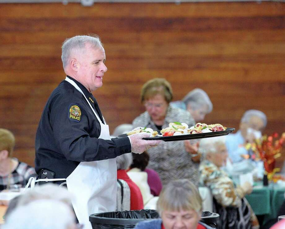 Greenwich Police Chief James Heavey serves Thanksgiving meals during the Greenwich Senior Center's annual Thanksgiving lunch party at the Eastern Greenwich Civic Center, Old Greenwich, Conn., Friday, Nov. 17, 2017. A traditional roasted turkey dinner was served by volunteers and Greenwich community leaders. Billy Lopez of Bridgeport provided the music and sang. Photo: Bob Luckey Jr. / Hearst Connecticut Media / Greenwich Time