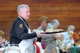 Greenwich Police Chief James Heavey serves Thanksgiving meals during the Greenwich Senior Center's annual Thanksgiving lunch party at the Eastern Greenwich Civic Center, Old Greenwich, Conn., Friday, Nov. 17, 2017. A traditional roasted turkey dinner was served by volunteers and Greenwich community leaders. Billy Lopez of Bridgeport provided the music and sang.