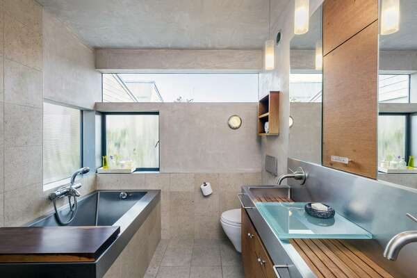 Stainless steel and timber accents finish the master bathroom.