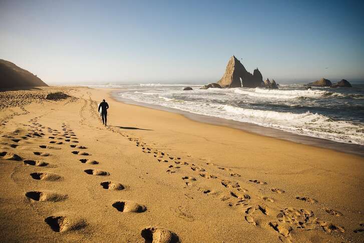 Jameson Kenway walks back to his car for work after an hour of surfing at Martins Beach in Half Moon Bay, Calif. Thursday, October 26, 2017.