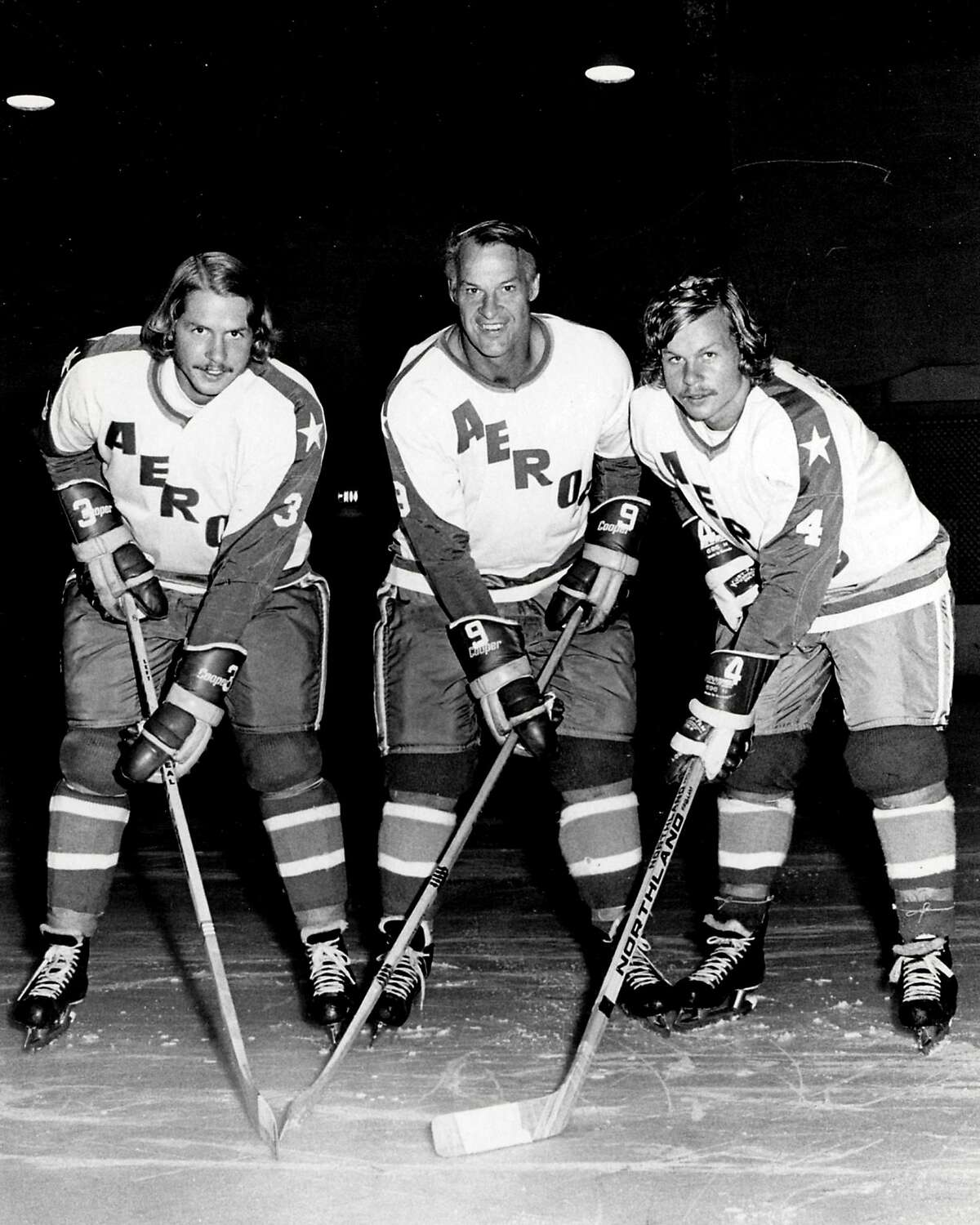 """FILE - In this Aug. 3, 1973, file photo, former Detroit Red Wings great Gordie Howe, center, is flanked by sons Marty, left, and Mark as they try their new Houston Aeros uniforms in St. Clair Shores, Mich. Gordie Howe, the hockey great who set scoring records that stood for decades, has died. He was 88. Son Murray Howe confirmed the death Friday, June 10, 2016, texting to The Associated Press: """"Mr Hockey left peacefully, beautifully, and w no regrets."""" (AP Photo/The Macomb Daily, David Posavetz, File)"""