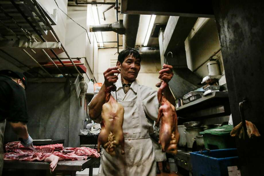 Rong Jian Guan carries ducks to a cylindrical oven to roast at Hing Lung meat shop in S.F.'s Chinatown. Photo: Gabrielle Lurie, The Chronicle