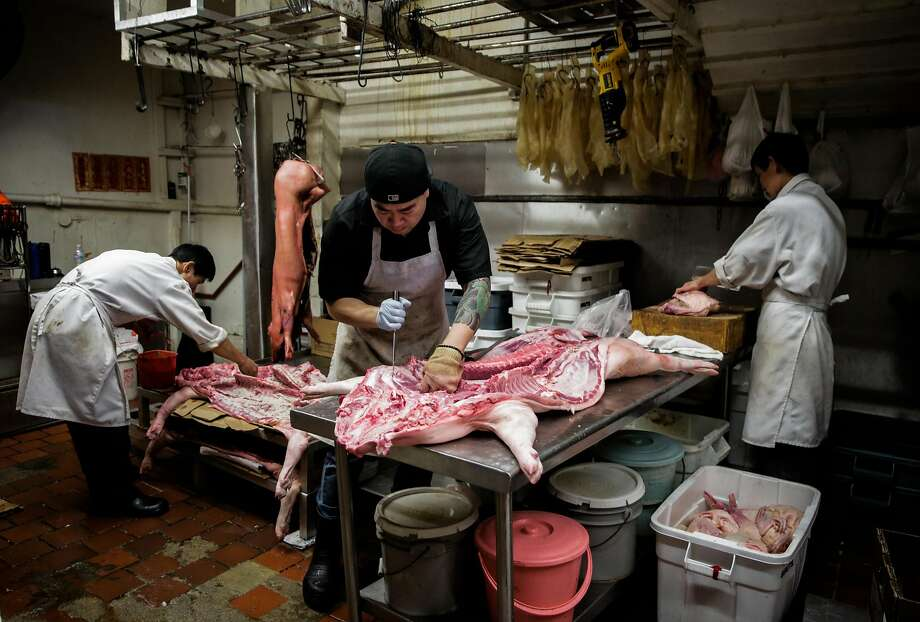 Simon Cheung (center) prepares a pig at Hing Lung Co. meat shop in S.F.'s Chinatown. Photo: Gabrielle Lurie, The Chronicle