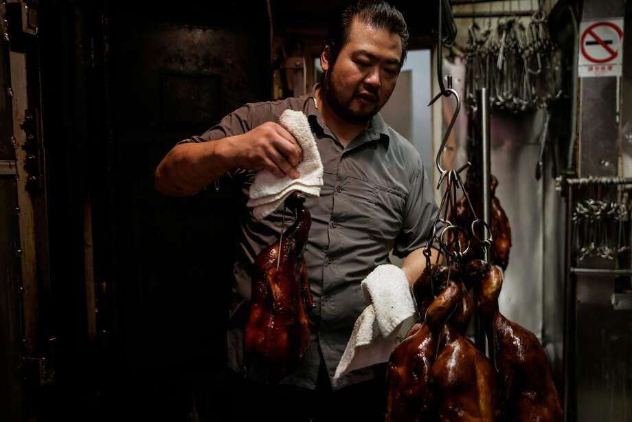 Eric Cheung hangs roasted duck at Hing Lung meat shop in Chinatown in San Francisco, Calif., on Tuesday, Nov. 7, 2017. Photo: Gabrielle Lurie, The Chronicle