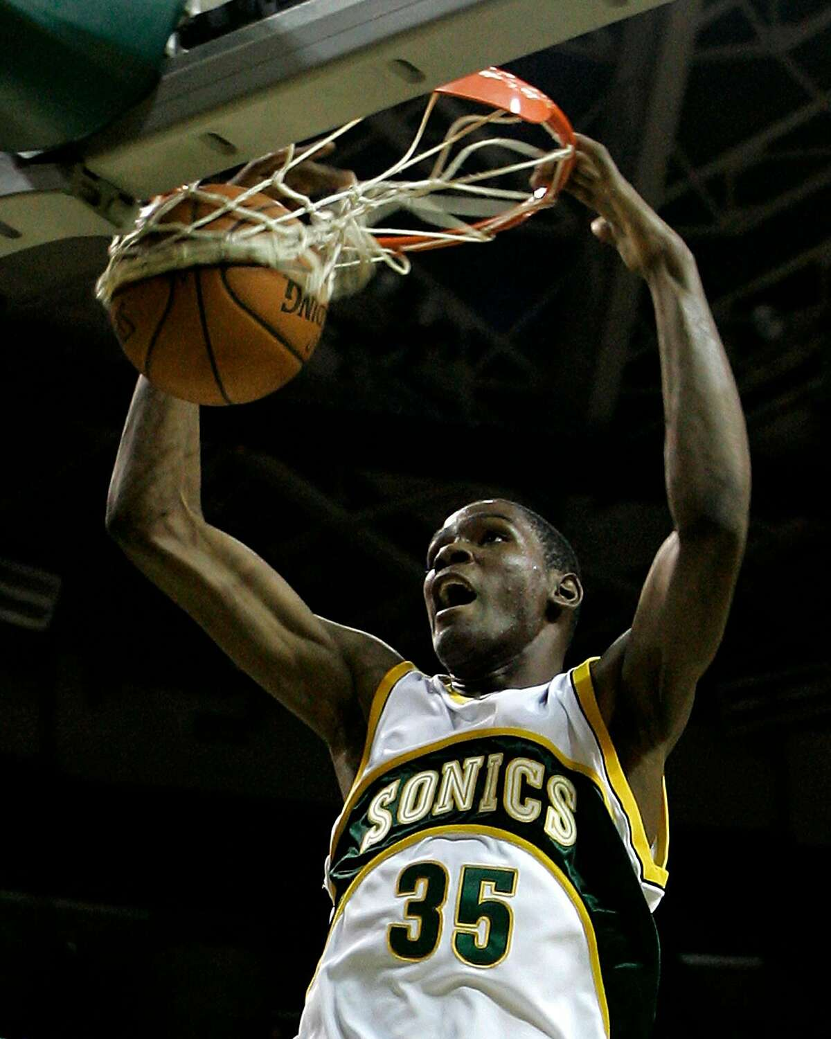 Seattle SuperSonics forward Kevin Durant dunks in the second quarter of an NBA basketball exhibition game as Golden State Warriors' Baron Davis, left, and Al Harrington, right, look on along with Sonics' Wally Szczerbiak, second from right, Tuesday, Oct. 23, 2007, at KeyArena in Seattle. (AP Photo/Ted S. Warren)
