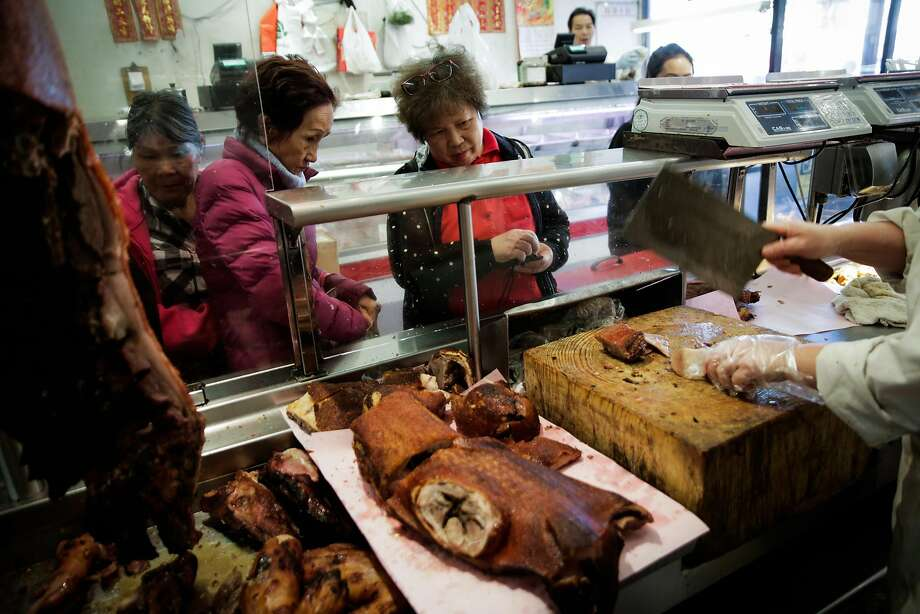 Customers watch as Rui Juan Tan (right) chops pork at Hing Lung Co. meat shop in S.F.'s Chinatown. Photo: Gabrielle Lurie, The Chronicle
