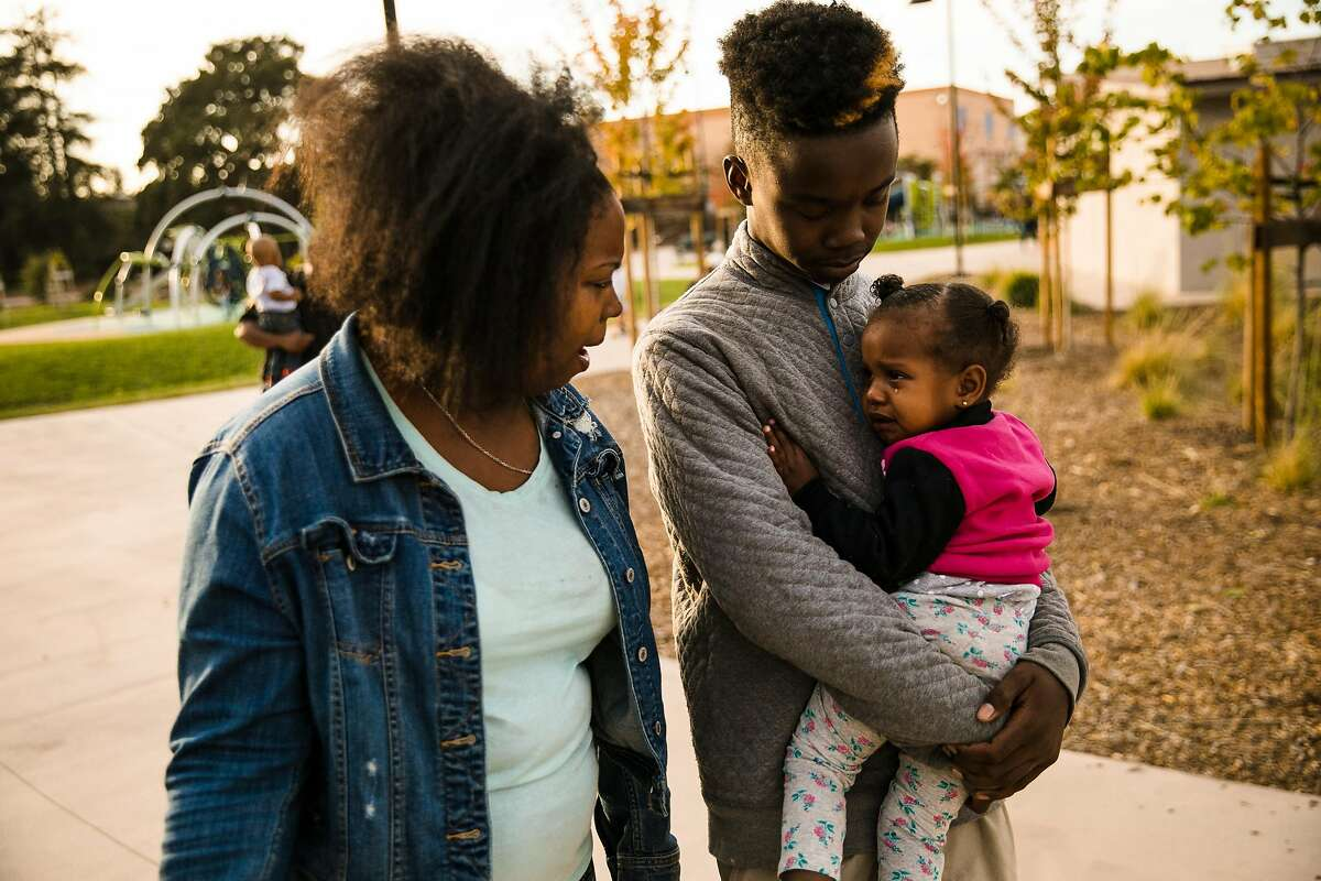 Jarae Rutledge, 14, LeAna Wade's oldest son, embraces his little sister, LeAni Wade, 2, as LeAna Wade comforts her at the Siempre Verde Park in Oakland, Calif. Tuesday, October 10, 2017.