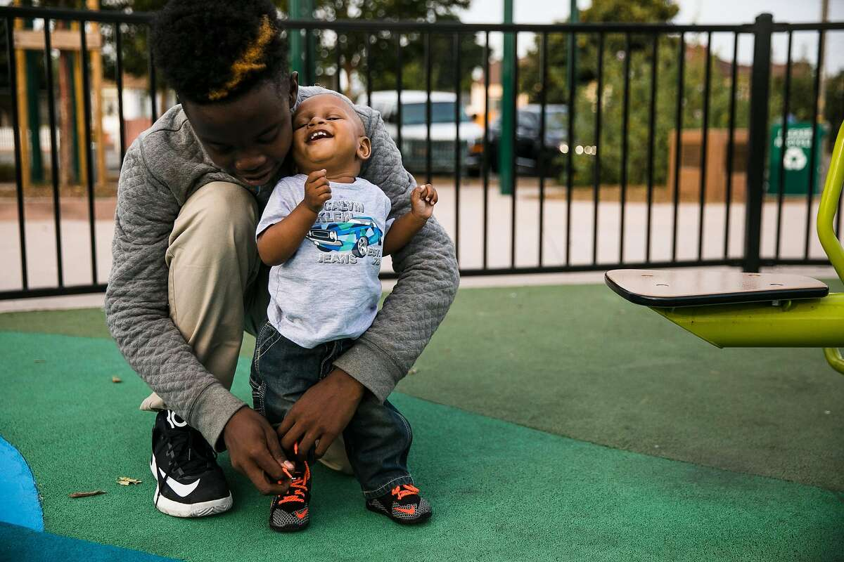 Jarae Rutledge, 14, LeAna Wade's oldest son, helps tie the shoes of his younger brother, Mason Wade, 1, on the playgrounds at the Siempre Verde Park in Oakland, Calif. Tuesday, October 10, 2017.
