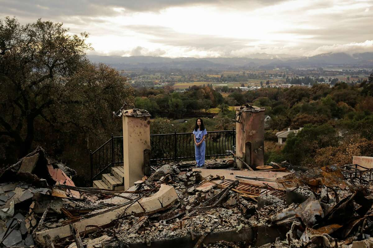 Dr. Stephanie Huang stands for a portrait at her home which was destroyed in the Tubbs fire in the Fountain Grove neighborhood of Santa Rosa, Calif., on Thursday, Nov. 16, 2017. Stephanie has still not bought herself new clothes and has been wearing her medical scrubs everyday since the fire.