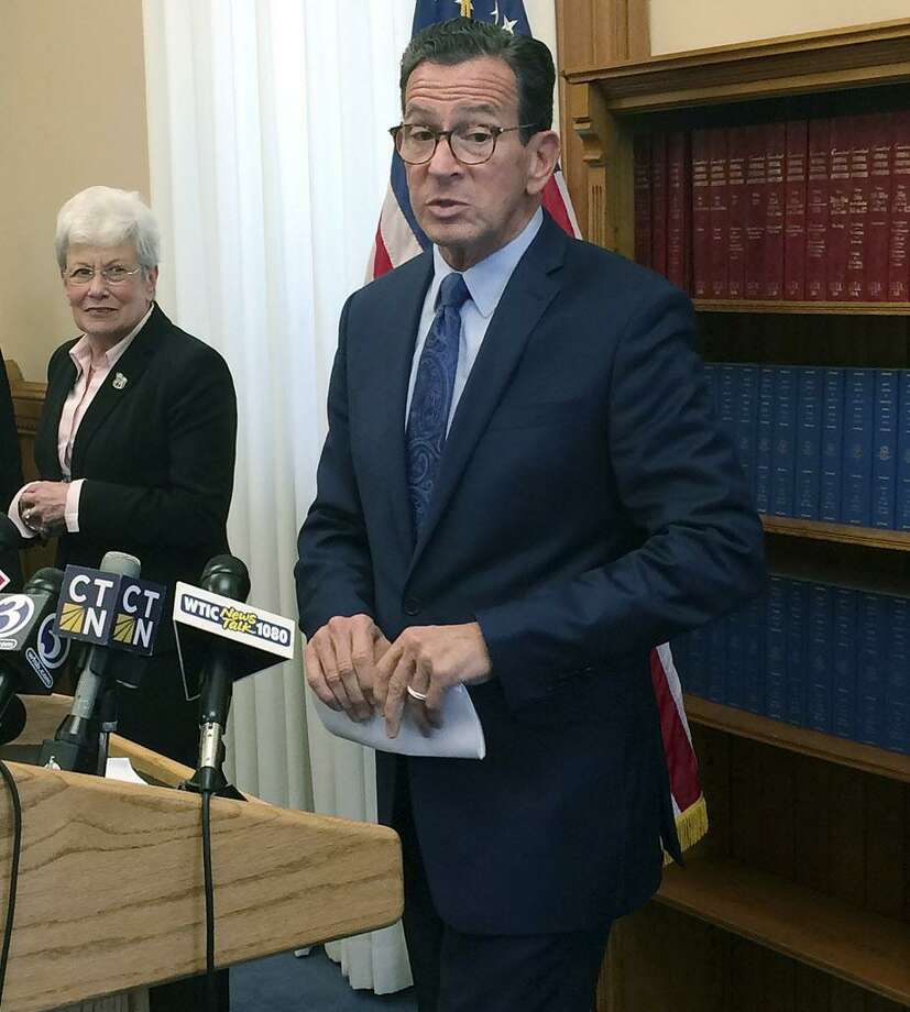Connecticut Gov. Dannel P. Malloy stands with Lt. Gov. Nancy Wyman, left, during a news conference at the Capitol, Tuesday, Oct. 31, 2017, in Hartford, Conn., after he announced on Twitter that he had signed a bipartisan state budget, but used his limited line-item veto power to scrap portions of the legislation related to a problematic tax on Connecticut's hospitals. (AP Photo/Susan Haigh) Photo: Susan Haigh / Associated Press / Copyright 2017 The Associated Press. All rights reserved.
