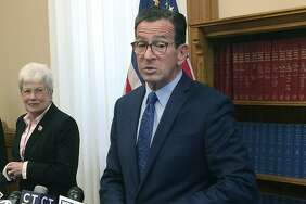 Connecticut Gov. Dannel P. Malloy stands with Lt. Gov. Nancy Wyman, left, during a news conference at the Capitol, Tuesday, Oct. 31, 2017, in Hartford, Conn., after he announced on Twitter that he had signed a bipartisan state budget, but used his limited line-item veto power to scrap portions of the legislation related to a problematic tax on Connecticut's hospitals. (AP Photo/Susan Haigh)
