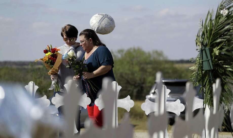Texas leaders, how many deaths is too many before you acknowledge that the common denominator in mass shootings is the ready availability of guns? Here, Randi Ray Rivera (left) and Belenda McLauren visit a makeshift memorial near the scene of the shooting at the First Baptist Church of Sutherland Springs. Twenty-six dead and 20 others wounded. Is that too many? Photo: Eric Gay / Associated Press / Copyright 2017 The Associated Press. All rights reserved.