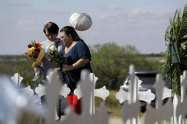 Texas leaders, how many deaths is too many before you acknowledge that the common denominator in mass shootings is the ready availability of guns? Here, Randi Ray Rivera (left) and Belenda McLauren visit a makeshift memorial near the scene of the shooting at the First Baptist Church of Sutherland Springs. Twenty-six dead and 20 others wounded. Is that too many?