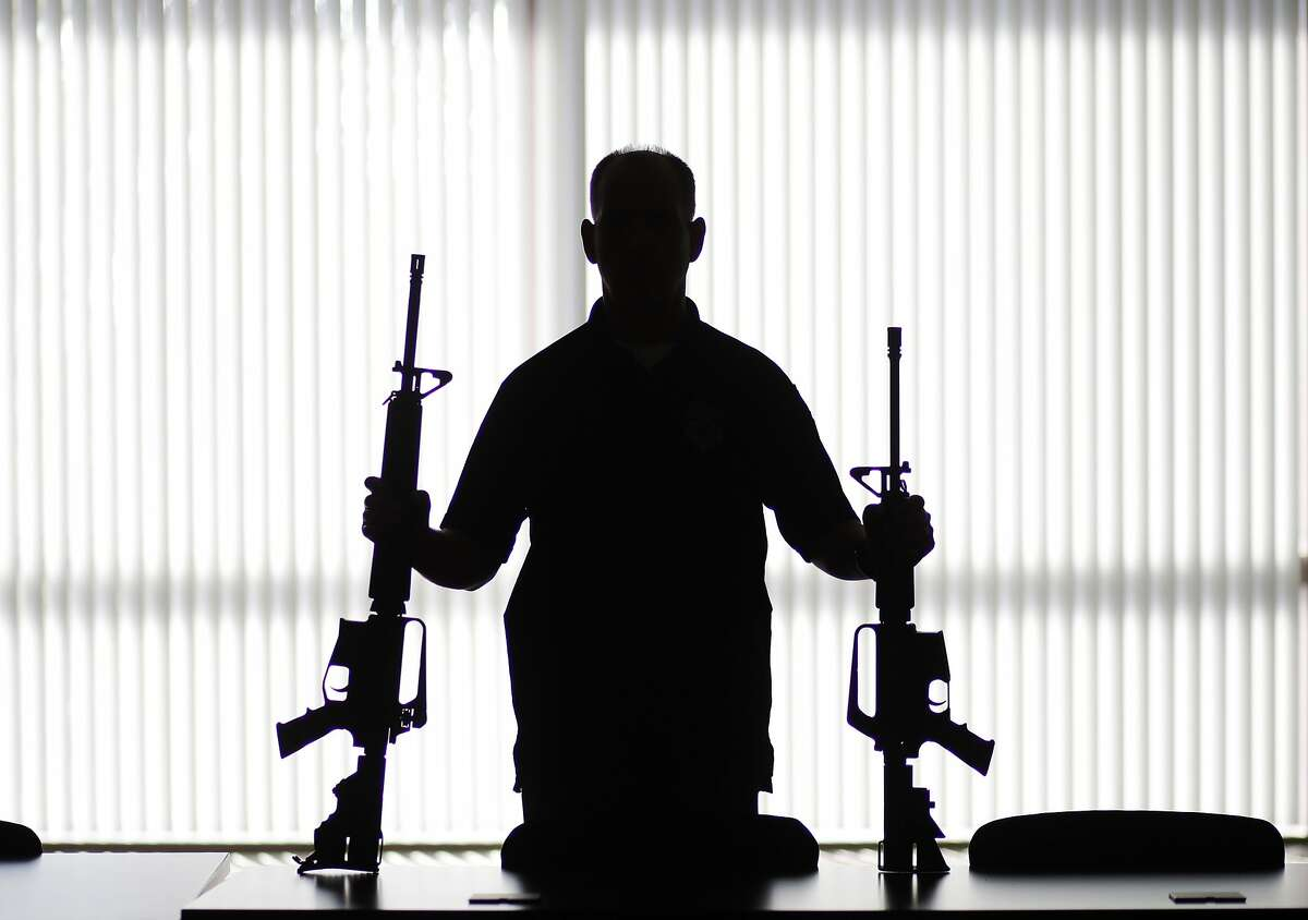 """In this Aug. 29, 2017, photo, an ATF agent poses with homemade rifles, or """"ghost guns,"""" at an ATF field office in Glendale, Calif. Police say Kevin Neal, who was barred from having guns because of a restraining order, made the two high-powered rifles he used in his shooting rampage in Northern California on Tuesday, Nov. 14. (AP Photo/Jae C. Hong)"""