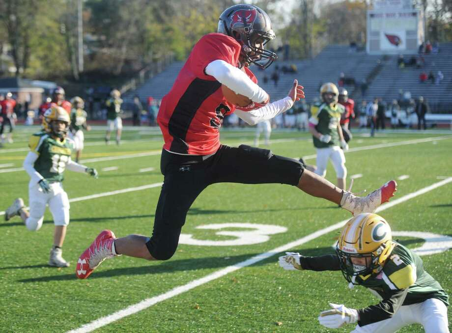 Jason Agudelo, 13, hurdles a defender during the BANC Raiders' junior high school football playoff game at Greenwich High School in Greenwich, Conn. Sunday, Nov. 12, 2017. The team was beaten by the undefeated Cos Cob Crushers in their opening round game Sunday, but has steadily progressed over the last few years against the odds. The Raiders made the GYFL playoffs for the first time this season after finishing the regular season with a 3-5 record despite having only 15 players on the team. Three years ago, head coach Richard Muskus Jr. came on because the team needed a coach and the team went winless in its first year and logged two wins last year. Photo: Tyler Sizemore / Hearst Connecticut Media / Greenwich Time