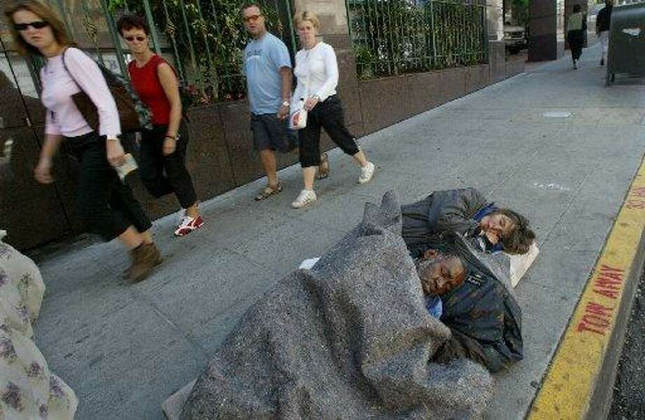Tourists walk past a man people sleeping on Ellis Street in S.F. Photo: Brant Ward / The Chronicle