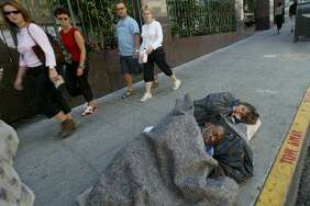 Tourists walk past a man people sleeping on Ellis Street in S.F.