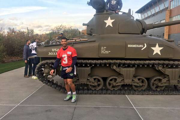 Seahawks quarterback Russell Wilson poses in front of an M4 Sherman tank after practice at the Virginia Mason Athletic Center on Friday afternoon in Renton. The tank is part of Seattle's Salute to Service campaign.