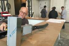 Joe DiSalvatore, owner of MFI Enterprises of Islandia, N.Y., installs bar equipment in the former People's Bank building in downtown Bridgeport which will soon reopen as a beer hall.