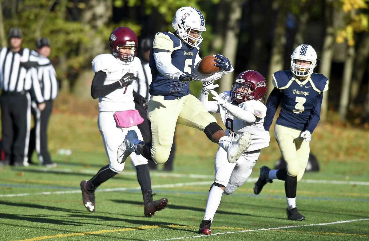 King running back Evan Townsend-Henry leaps in for a touchdown against St. Lukes Koy Price in a FAA regular season football final in Stamford, Connecticut on Saturday, Nov. 11, 2017. King defeated St. Lukes 42-13.