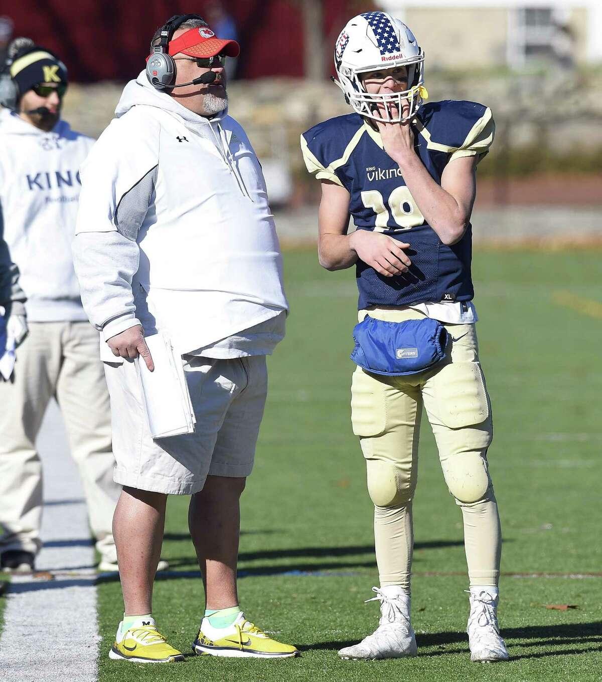 King coach Dan Gouin talks with quarterback Renn Lints (19) in a FAA regular season football final against St. Lukes in Stamford, Connecticut on Saturday, Nov. 11, 2017. King defeated St. Lukes 42-13.