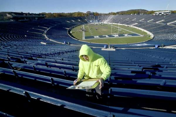 """Larry McKenna, a Giordano Construction project supervisor, inspects wooden seating at Yale Bowl on Friday as Yale prepares for """"The Game"""" against Harvard."""
