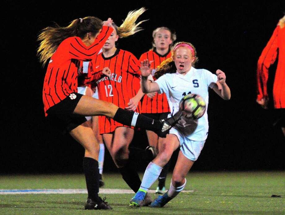 Staples' Autumn Smith blocks a kick by Ridgefield's Kathryn Barlow. Photo: Christian Abraham / Hearst Connecticut Media / Connecticut Post