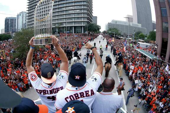 World Series MVP George Springer, left, hoists the World Series trophy alongside teammate Carlos Correa and Mayor Sylvester Turner as they ride atop a firetruck during a parade honoring the MLB champions earlier this month.