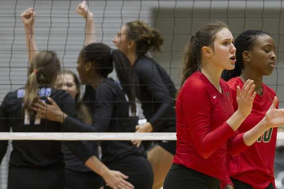 The Woodlands outside hitter Courtney Heiser, center, reacts alongside middle blocker Amanda Ifeanyi after losing to Lewisville Hebron in straight sets during a Class 6A semifinal volleyball match at the UIL state tournament, Friday, Nov. 17, 2017, in Garland.
